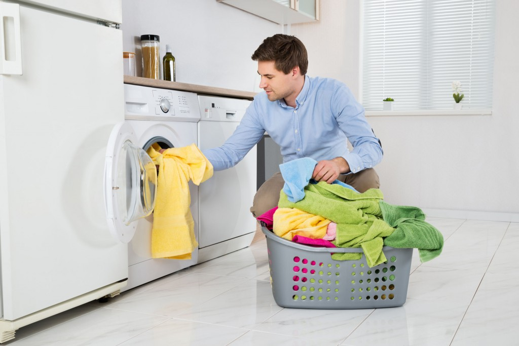 43082872 - young man loading clothes into washing machine in kitchen